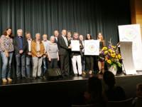 Bürgermeister Altenberger nimmt mit Mitarbeitern und Gemeinderäten die Plakette entgegen