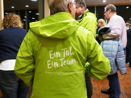 """Teilnehmer probieren die Regenjacke mit der Aufschrift """"Ein Tal, ein Team"""""""