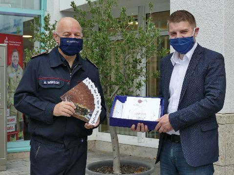 Feuerwehrkommandant Andreas Wersch nimmt die Gutscheine von Bürgermeister Benedikt Paulowitsch entgegen.