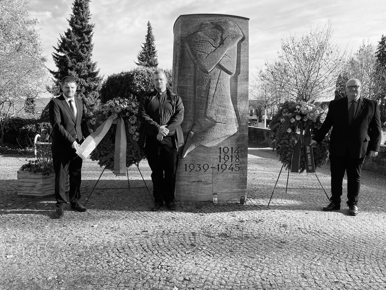Bürgeremeister Paulowitsch mit Pfarrer Maisenbacher und Udo Rauhut (VdK) bei der Kranzniederlegung am Mahnmal in Rommelshausen.